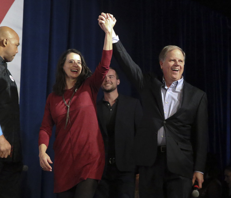 Photo - Democratic Candidate for U.S. Senate Doug Jones and his wife Louise wave to supporters as they walk on stage during a rally Monday, Dec. 11, 2017, in Birmingham, Ala. Jones is facing Republican Roy Moore. (AP Photo/John Bazemore)