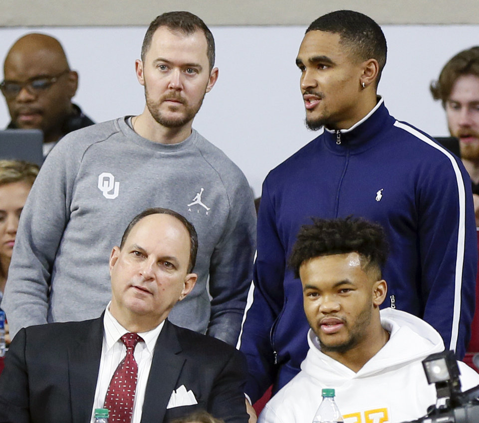 Photo - OU quarterback Jalen Hurts, upper right, talks to football coach Lincoln Riley as they stand behind OU athletic director Joe Castiglione and Heisman-winning quarterback Kyler Murray during a men's college basketball game between the Oklahoma Sooners and the Texas Longhorns at the Lloyd Noble Center in Norman, Okla., Saturday, Feb. 23, 2019. Photo by Nate Billings, The Oklahoman