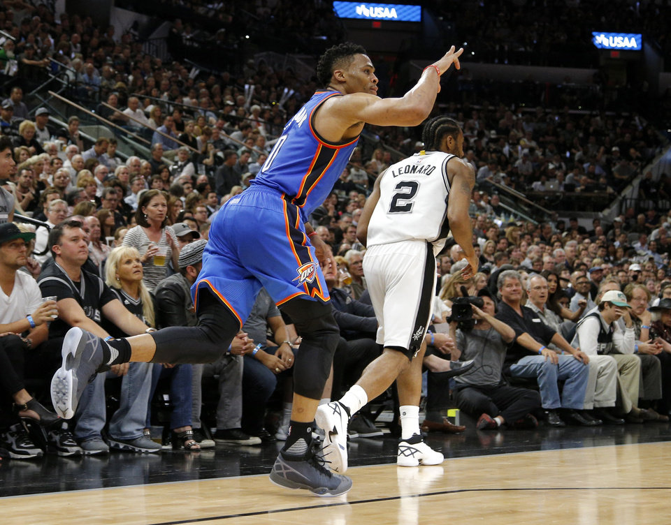 Photo - Oklahoma City's Russell Westbrook (0) celebrates after a basket behind San Antonio's Kawhi Leonard (2) during Game 5 of the second-round series between the Oklahoma City Thunder and the San Antonio Spurs in the NBA playoffs at the AT&T Center in San Antonio, Tuesday, May 10, 2016. Oklahoma City won 95-91. Photo by Bryan Terry, The Oklahoman