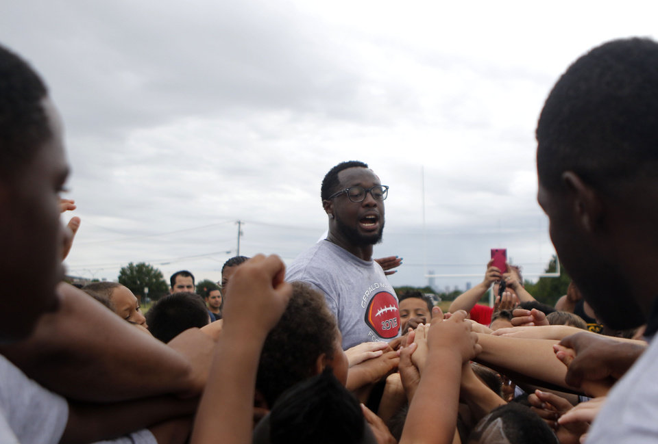 Photo - Gerald McCoy gets the kids in a huddle during the 2015 Gerald McCoy Football Camp at Webster Middle School in Oklahoma City on Friday June 13, 2015.  Photo by Jackie Dobson, The Oklahoman.
