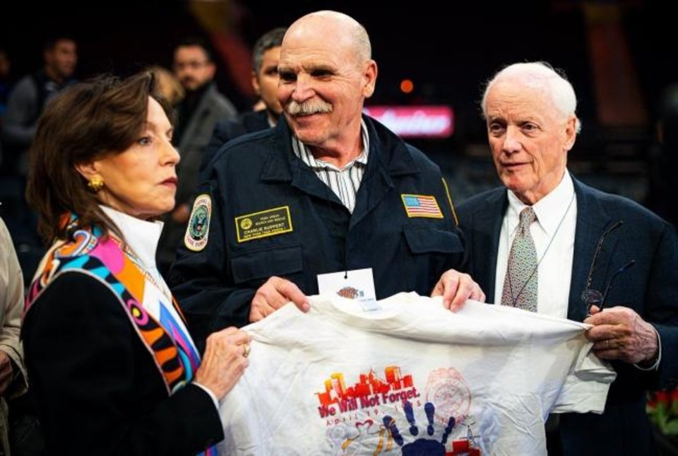 Photo -  Former Oklahoma Gov. Frank Keating, right, and First Lady Cathy Keating hold a T-shirt to commemorate the 1995 Oklahoma City bombing with Charlie Ruppert of FEMA on Friday at Madison Square Garden in New York. [ZACH BEEKER/NBAE VIA GETTY IMAGES]