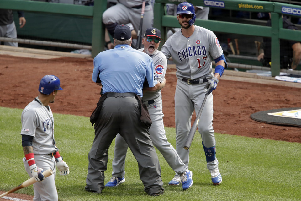 Photo -  Cubs manager Joe Maddon, center, yells toward the Pirates dugout as he is restrained by umpire Joe West and Chicago's Kris Bryant (17) during the fourth inning July 4 in Pittsburgh. Maddon was ejected. The Cubs and Pirates are in the thick of the NL Central race, which should have a lively second half. [Gene J. Puskar/the associated press]