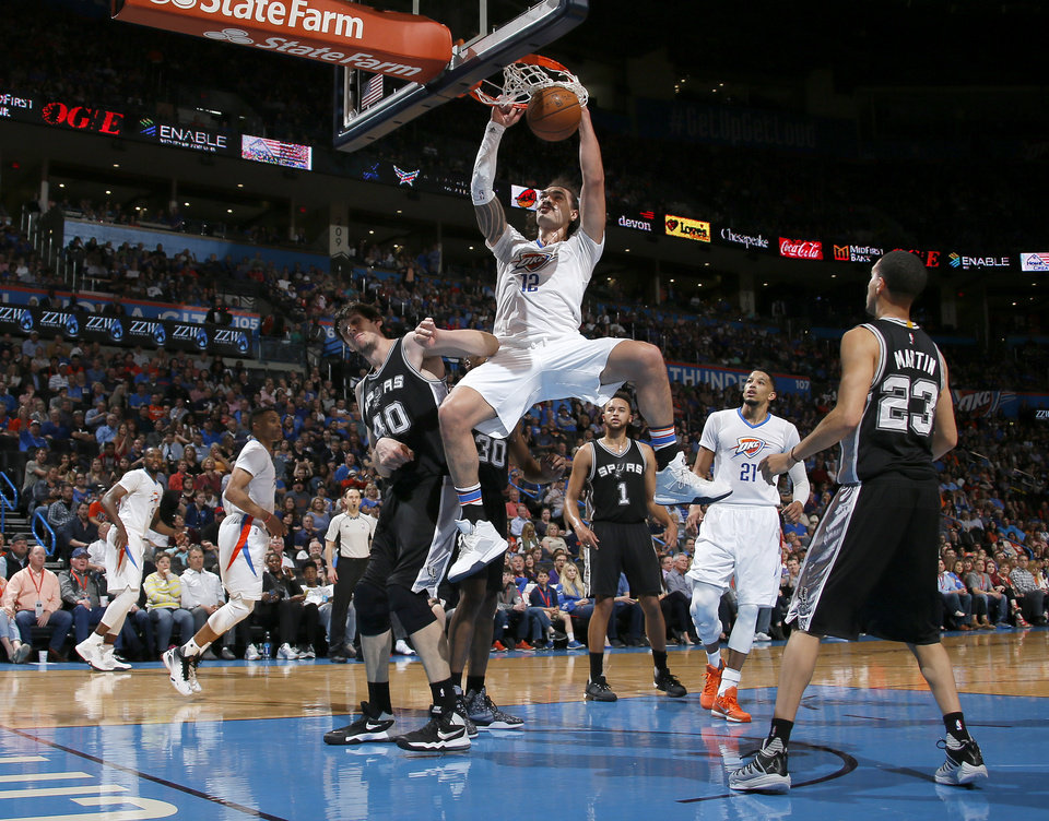 Photo - Oklahoma City's Steven Adams (12) dunks the ball beside San Antonio's Boban Marjanovic (40) during an NBA basketball game between the Oklahoma City Thunder and the San Antonio Spurs at Chesapeake Energy Arena in Oklahoma City, Saturday, March 26, 2016. Oklahoma City won 11-92. Photo by Bryan Terry, The Oklahoman