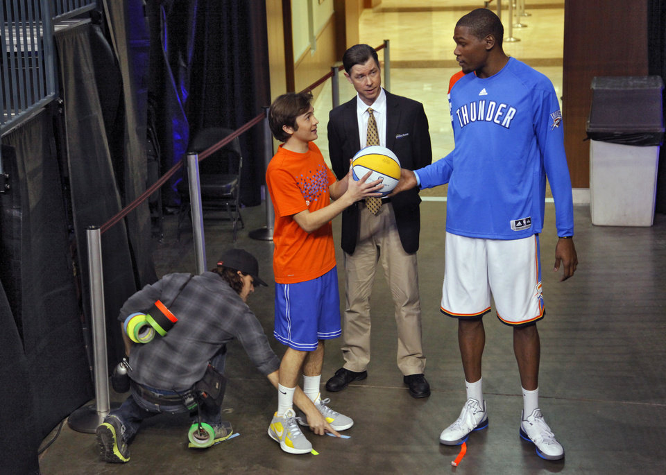 Photo - Oklahoma City Thunder's Kevin Durant works with actors Taylor Gray, left, and Timothy Fall as a member of the crew marks spots on the set of his movie 'Thunderstruck' inside the Chesapeake Energy Arena on Tuesday, Jan. 24, 2012, in Oklahoma City, Okla. Photo by Chris Landsberger, The Oklahoman