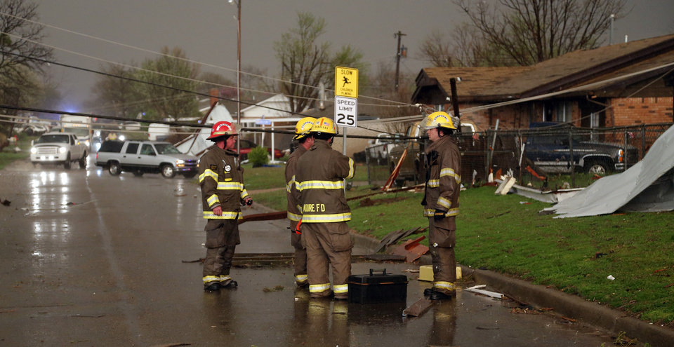 Photo - Moore fire fighters work the scene of a downed power line after a tornado hit in Moore, Okla. on Wednesday, March 25, 2015.  Photo by Chris Landsberger, The Oklahoman