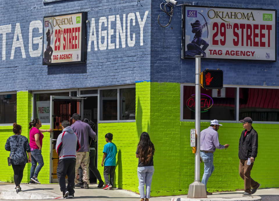 Photo - Customers stand outside the 29th St. Tag Agency as they wait in line for service in Oklahoma City, Okla. on Tuesday, March 31, 2020. The tag agency only allows 10 people inside the location at one time.  [Chris Landsberger/The Oklahoman]