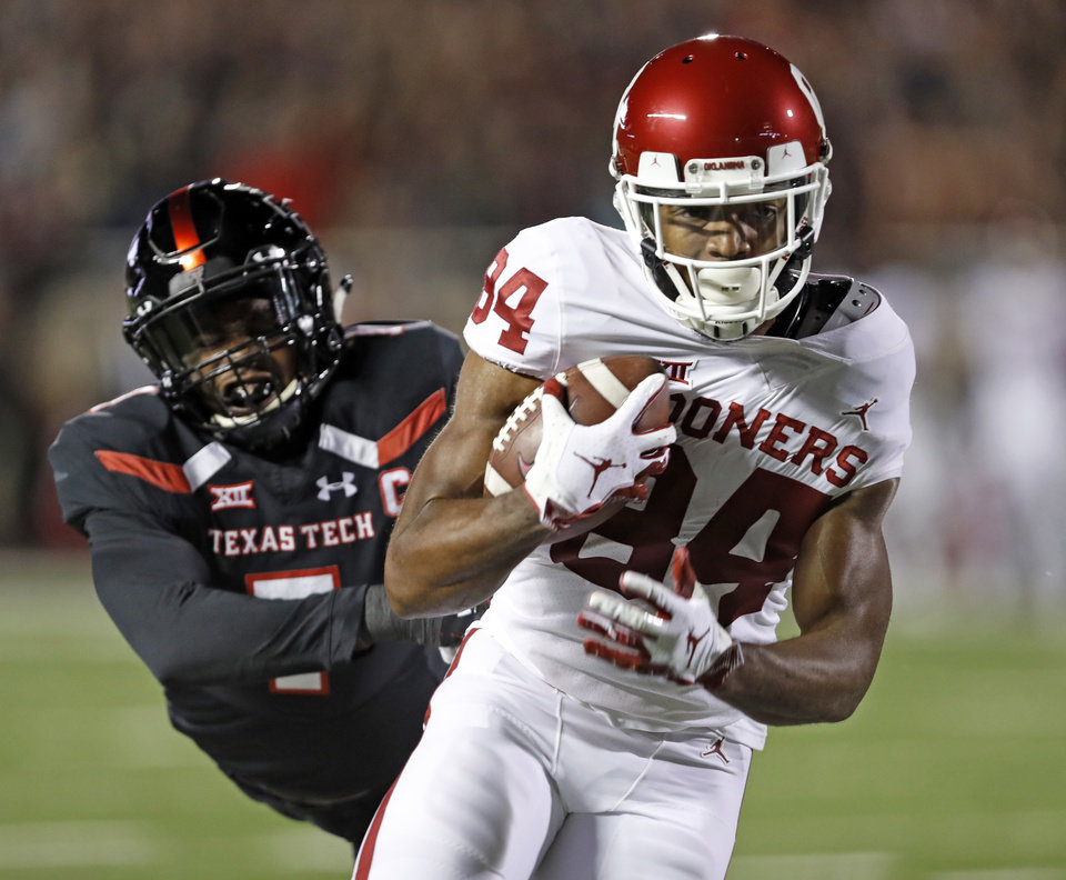 Photo - Oklahoma's Lee Morris (84) breaks away from Texas Tech's Jah'Shawn Johnson (7) to score a touchdown during the first half of an NCAA college football game Saturday, Nov. 3, 2018, in Lubbock, Texas. (AP Photo/Brad Tollefson)