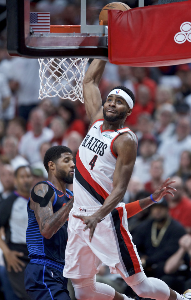 Photo - Portland Trail Blazers forward Maurice Harkless (4) dunks over Oklahoma City Thunder forward Paul George during the first half of Game 5 of an NBA basketball first-round playoff series, Tuesday, April 23, 2019, in Portland, Ore. (AP Photo/Craig Mitchelldyer)