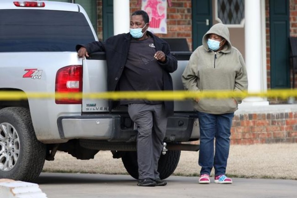 Photo -  A man and woman watch the scene of a suspected mass homicide where at least 5 children were slain Tuesday, Feb. 2, 2021 in Muskogee, Okla. The woman has a grandchild that lives at the home where the suspected homicides happened. [Photo by Mike Simons, Tulsa World]