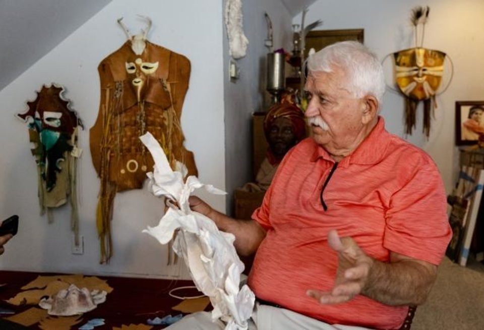 Photo -  Artist G. Patrick Riley talks about his artwork at his home studio in Bethany on July 29. Riley, who is renowned for his colorful masks, has a variety of his work on view in the exhibit