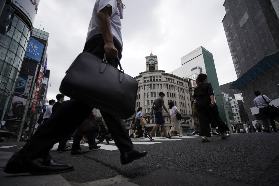 Photo -  People walk across a pedestrian crossing at Ginza shopping district in Tokyo Wednesday, June 24, 2020. Tokyo reported more than 50 new cases of the coronavirus on Wednesday, the largest number since early May, but officials say the jump does not mean an immediate return to business restrictions. (AP Photo/Eugene Hoshiko)