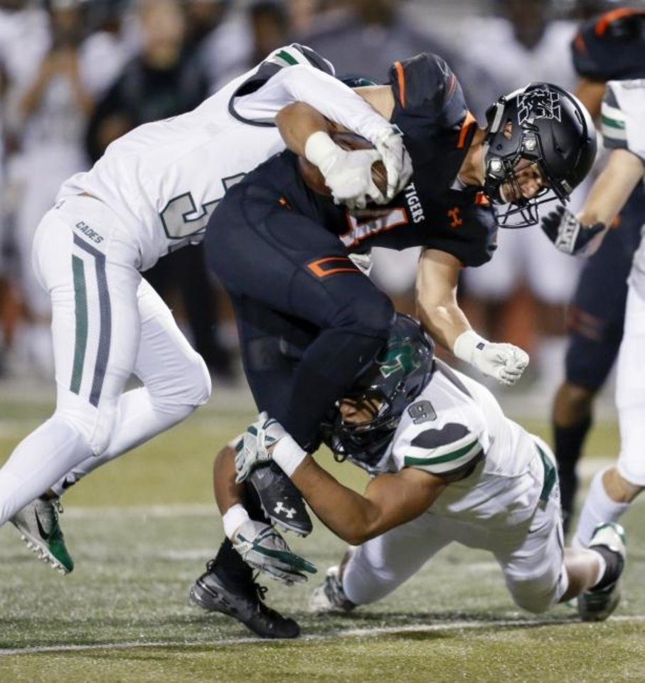 Photo -  Norman's Tyler Crump (4) is tackled by Edmond Santa Fe's Xavier Sutton (32), left, and James Burnett (9) during a 2018 game. [Nate Billings/The Oklahoman]