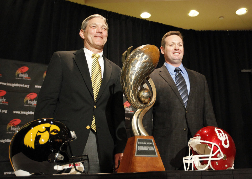 Photo - UNIVERSITY OF OKLAHOMA / OU / UNIVERSITY OF IOWA / COLLEGE FOOTBALL: Iowa head coach Kirk Ferentz and Oklahoma head coach Bob Stoops pose in front of the Insight Bowl trophy during a press conference for the Insight Bowl at the Camelback Inn in Paradise Valley, Ariz.,  Thursday, Dec. 29, 2011. Photo by Sarah Phipps, The Oklahoman