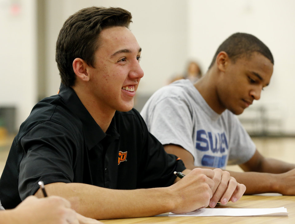Photo - John Kolar and Bo Garver make their college intentions known at Norman North High School on Wednesday, Feb. 4, 2015  in Norman, Okla. Photo by Steve Sisney, The Oklahoman