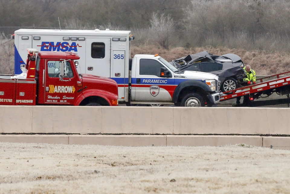 Photo - A wrecker removes a car involved in an accident on the entrance ramp to westbound I-44 near NW 63rd and I-235 as an ambulance leaves during freezing rain in Oklahoma City, Wednesday, Feb. 27, 2019. by Nate Billings, The Oklahoman