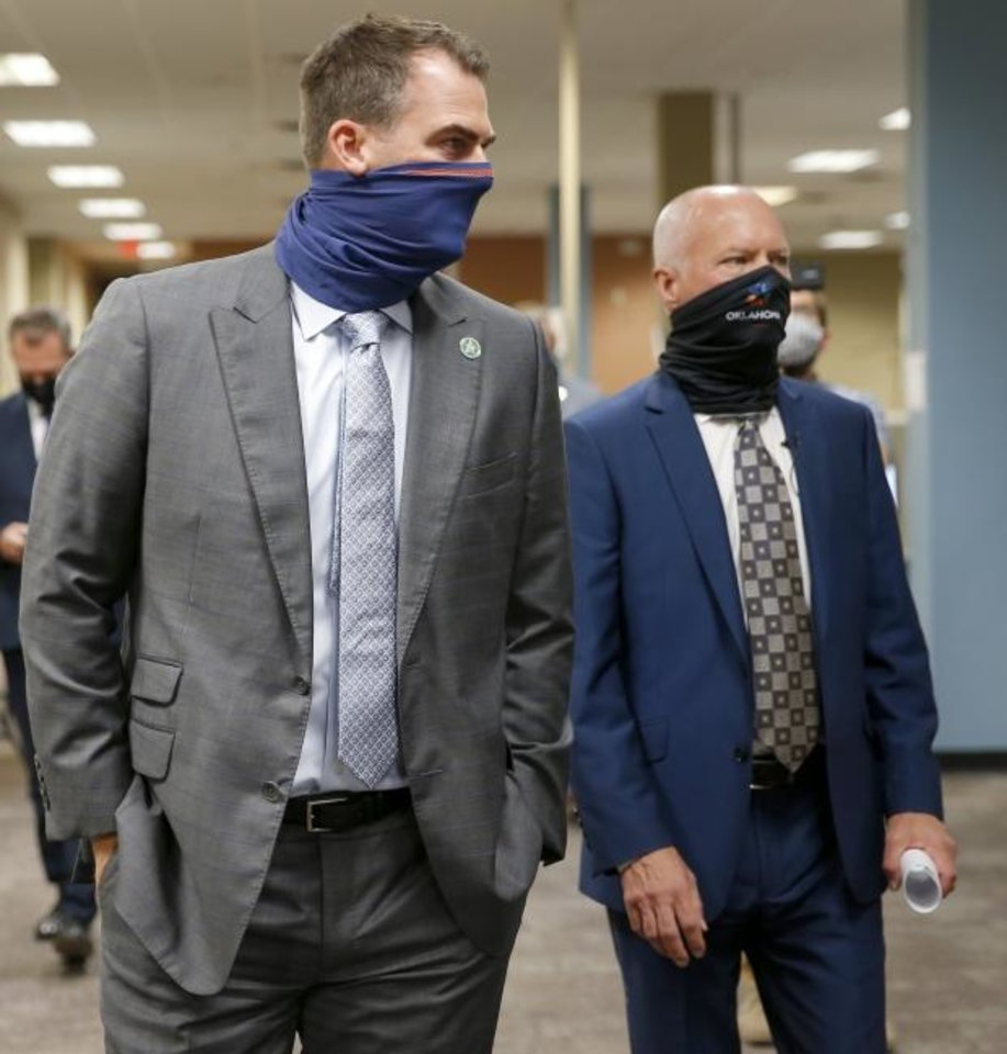 Photo -  Gov. Kevin Stitt, left, Oklahoma Health Commissioner Lance Frye, tour a new Oklahoma State Department of Health COVID-19 contact tracing center inside the old Shepherd Mall in Oklahoma City, Wednesday, Aug. 5, 2020. [Bryan Terry/The Oklahoman]