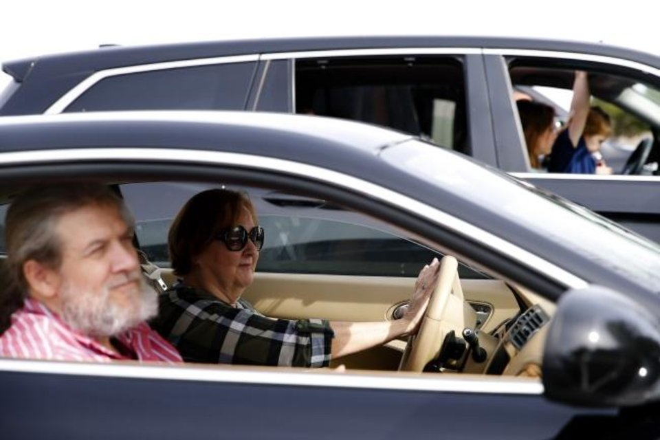 Photo -  Colleen Seiter honks her horn as she and her husband, Shawn, attend