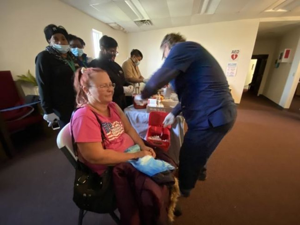 Photo -  Carrie Smith with Community Health Centers of Oklahoma watches as Tammy Abernathy receives a free flu shot by John Slayton, licensed practical nurse, at Ebenezer Baptist Church, 3600 N Kelley. [Carla Hinton/The Oklahoman]