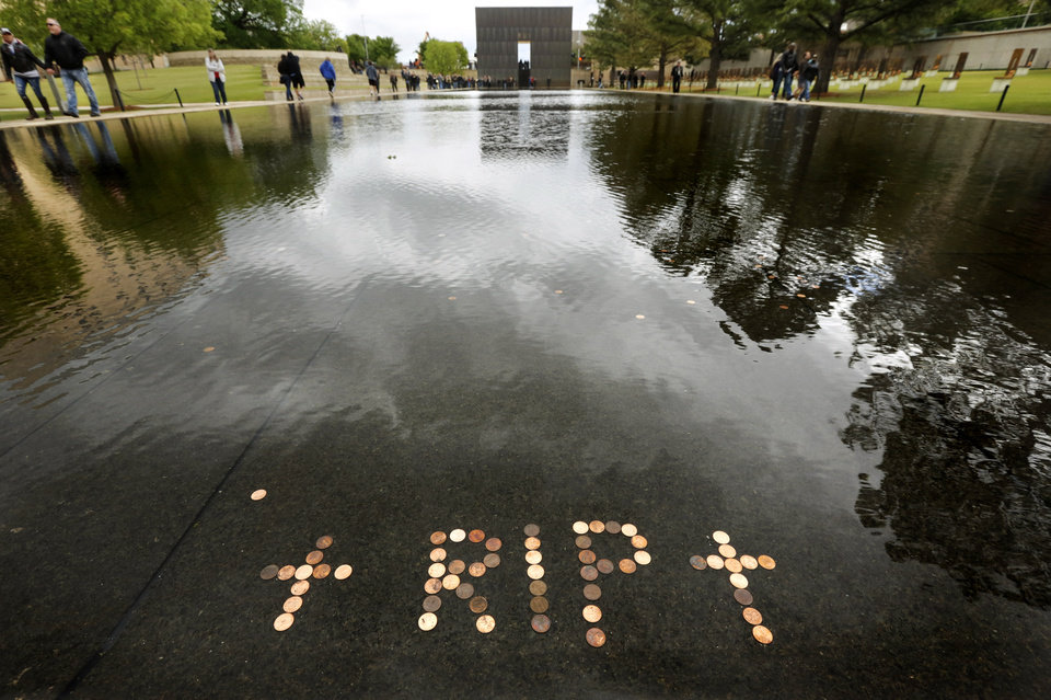Photo - Coins were placed in the Reflecting Pool to send a message of hope: the letters RIP between two crosses. Motorcyclists from across the country, numbering more than 1,000 strong, rumbled through the downtown streets of Oklahoma City on Saturday, April, 22, 2017,  taking part in  the 10th annual Ride to Remember.  The annual benefit run honors the 168 people killed in the April 19, 1995 bombing of the Alfred P. Murrah Federal Building. All funds raised go toward the Oklahoma City National Memorial and Museum, which operates solely on private donations. Bikers rolled out for the first event in 2007.    Photo by Jim Beckel, The Oklahoman