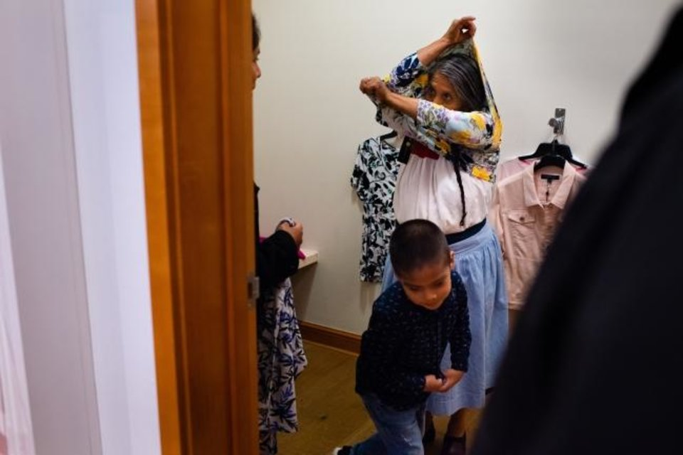 Photo -  Romero León tries on clothes at the mall in Fairview Heights. She is accompanied by daughter Guillermina Sánchez and son-in-law, Abdias Guardian, 39. Her grandson Andrew Guardian, 5, runs by. [Sarah L. Voisin/The Washington Post]
