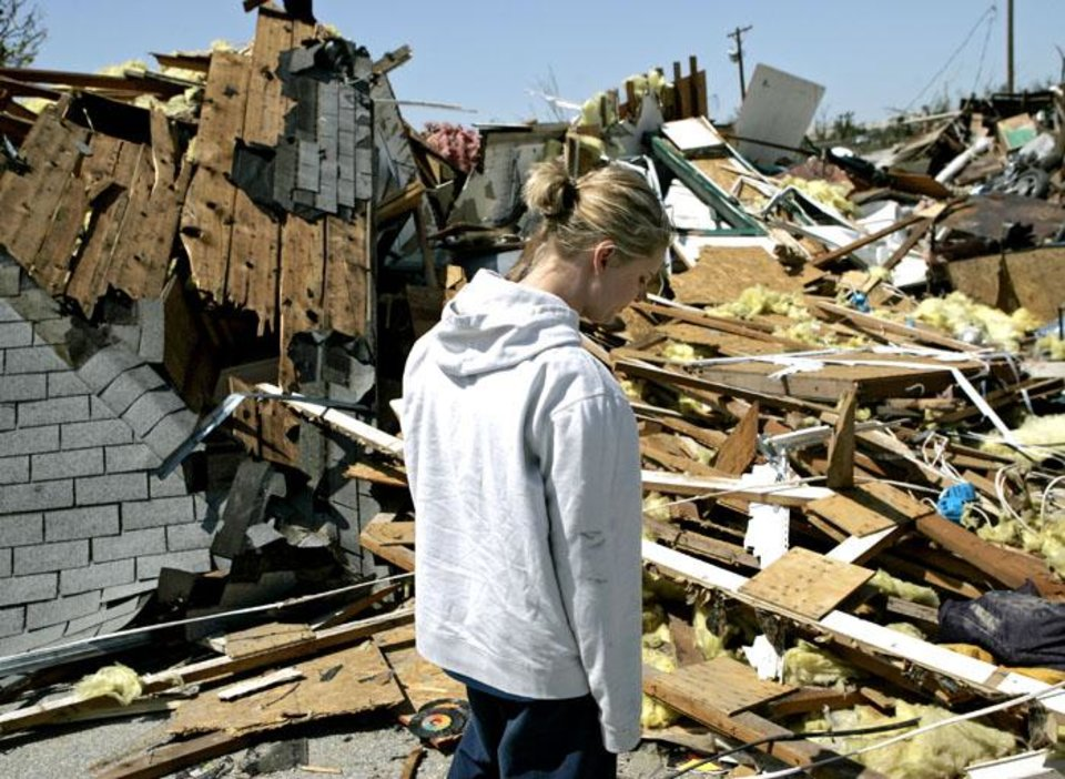 Photo -  TORNADO DAMAGE, HOUSE: Tressie Gilmore, 25, walks past the remains of her family's home on May,11, 2008, following a tornado that hit the area on Saturday. By John Clanton, The Oklahoman ORG XMIT: KOD