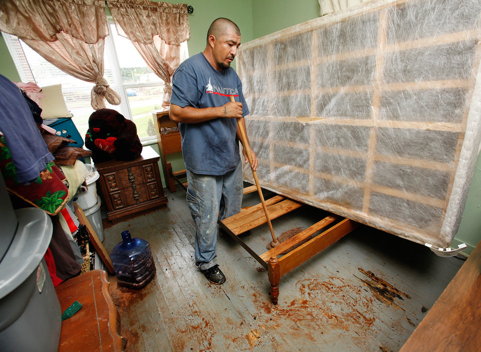 Photo - Abel Borrego mops muddy water from the floor of a bedroom in his house on the east bank of Lightning Creek near SW 28 and Santa Fe. Residents cleaned homes and yards in the area near Lightning Creek in south Oklahoma City, Friday, July 9, 2010. Heavy rains last night caused the  creek to overflow its banks, flooding the areas on both sides of the creek.  Staff Photo by Jim Beckel , The Oklahoman
