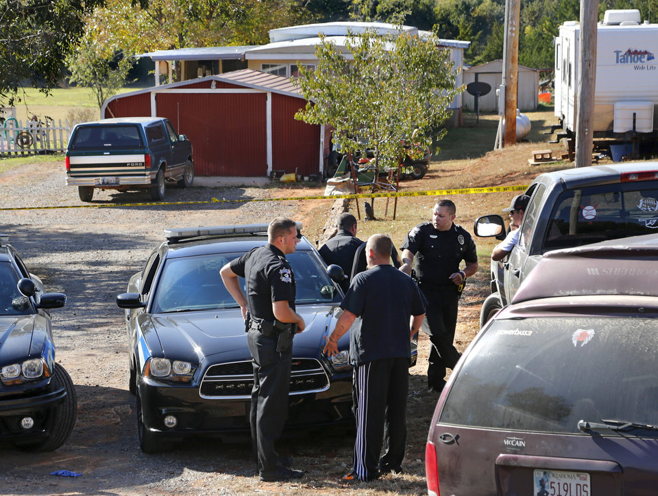 Photo - The scene at 17110 NE 206 in far northeast Oklahoma County, where the bodies of Ronald and Valerie Wilkson were discovered at their home late Sunday night after suspect Michael Dale Vance went on a shooting spree after he engaged in a shootout with Wellston police officers. The Wilkson couple are the aunt and uncle of Vance. In this photo, Oklahoma County sheriff's deputies talk on Monday, Oct. 24, to a man who said he was a relative of the victims. 