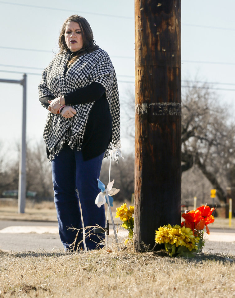 Photo - Sarah Burdine looks at a utility pole with flowers around it as a memorial to her son, Jean-Ciar Pierce, on Friday, Jan. 24, 2020, at Spencer Rd. and NE 23 in Spencer, Okla. [Nate Billings/The Oklahoman]