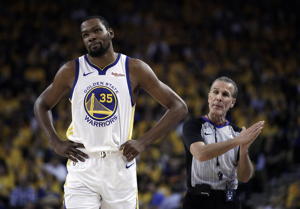 Photo - FILE - In this Wednesday, May 8, 2019, file photo, Golden State Warriors' Kevin Durant, left, walks away from referee Ken Mauer during the first half of Game 5 of the team's second-round NBA basketball playoff series against the Houston Rockets in Oakland, Calif. Durant is yet to progress to on-court work in his recovery from a strained right calf and won't be ready to return for Golden State in Game 1 of the NBA Finals on May 30. (AP Photo/Ben Margot, File)