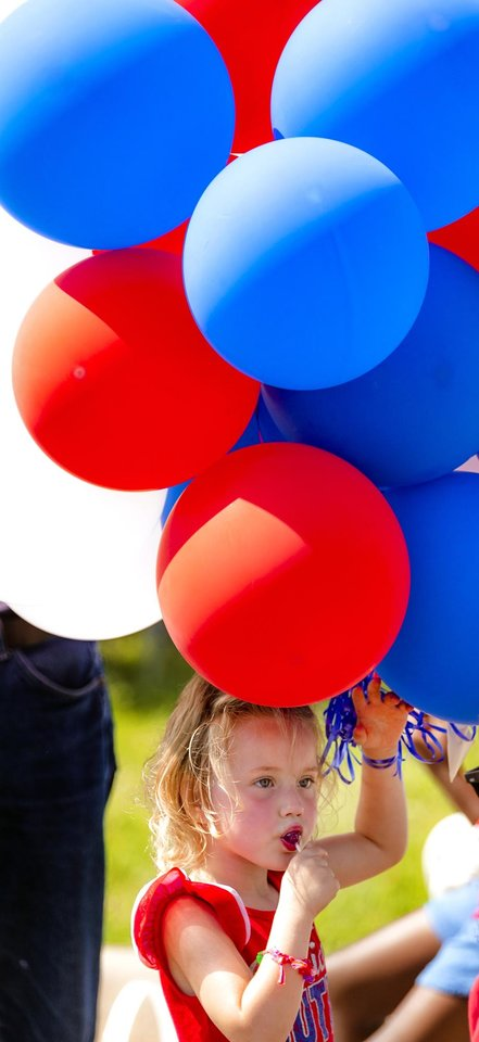 Photo - Brook Andres carries a bunch of balloons as she takes in the sights During the Bethany Freedom Festival parade in Bethany, Okla. on Thursday, July 4, 2019.    [Chris Landsberger/The Oklahoman]