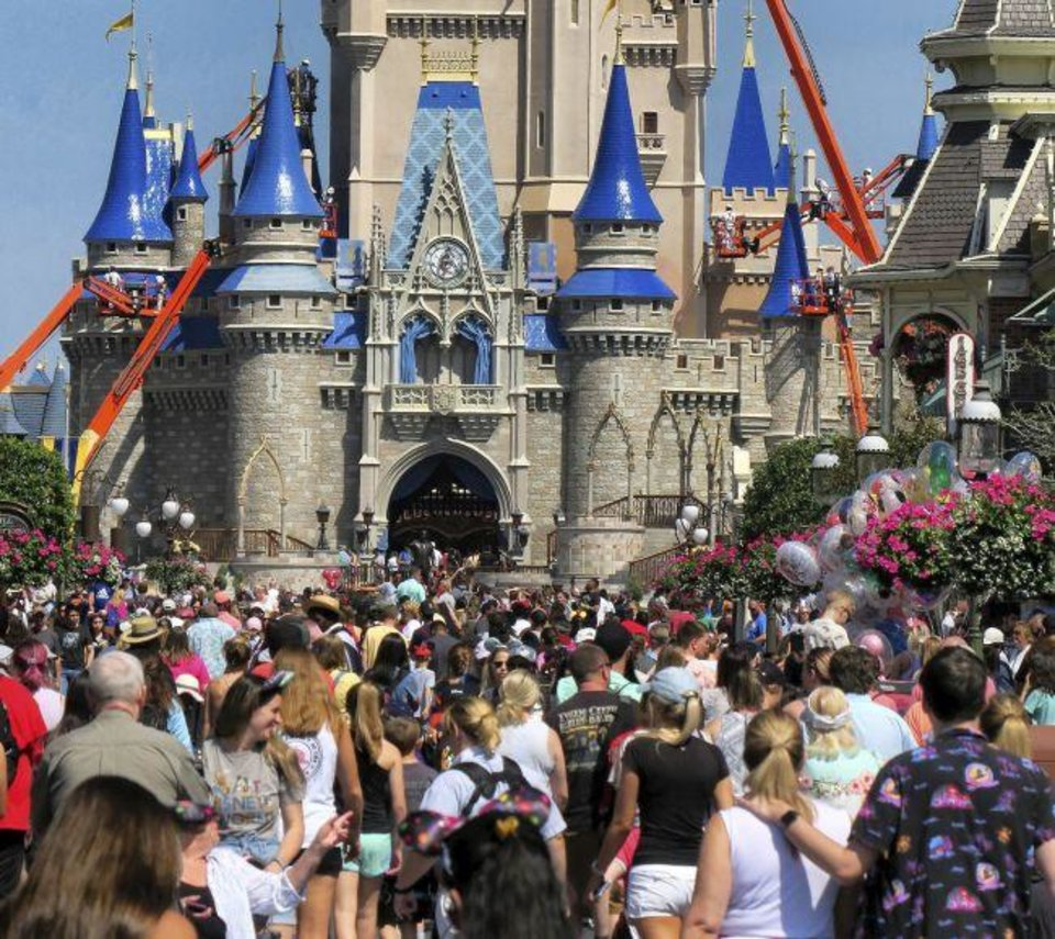 "Photo -  FILE - In this March 12, 2020, file photo, a crowd is shown along Main Street USA in front of Cinderella Castle in the Magic Kingdom at Walt Disney World in Lake Buena Vista, Fla. As Walt Disney World prepares to allow some third-party shops and restaurants to open at its entertainment complex later this week, it's posting a warning. While enhanced safety measures are being taken at Disney Springs, ""an inherent risk of exposure to COVID-19 exists in any public place where people are present,"