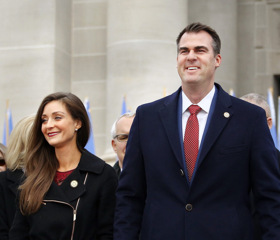Photo - Kevin Stitt and wife, Sarah, at his inauguration where he was sworn in as Oklahoma's 28th governor by Supreme Court Chief Justice Noma Gurich on Monday, Jan. 14, 2019.  Photo by Jim Beckel, The Oklahoman.