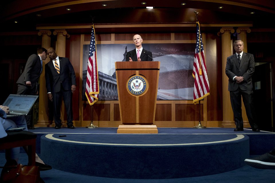 "Photo - Sen. Rick Scott, R-Fla., left, accompanied by Sen. Ben Sasse, R-Neb., left, Sen. Tim Scott, R-S.C., second from left, and Sen. Lindsey Graham, R-S.C., right, speaks at a news conference about the coronavirus relief bill on Capitol Hill in Washington, Wednesday, March 25, 2020. Senators discussed what they are calling a ""drafting error"" in the 2 trillion dollar stimulus bill. (AP Photo/Andrew Harnik)"