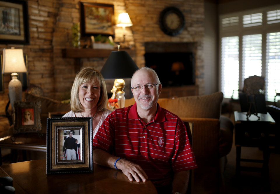 Photo - Mike and Marilyn Riley pose for a photo with a picture of their son Lincoln Riley, Oklahoma's offensive coordinator inside their home in Muleshoe, Texas, on Thursday, June 25, 2015. Photo by Bryan Terry, The Oklahoman