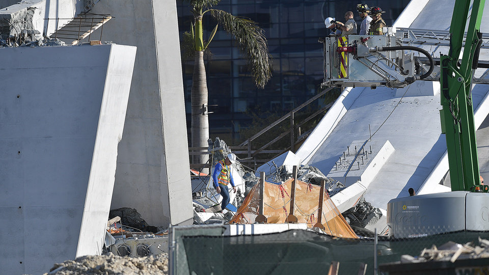 Photo - Miam-Dade Fire Rescue personnel work after a brand new, 950-ton pedestrian bridge collapsed in front of Florida International University, Thursday, March 15, 2018, in Miami. Florida officials said Thursday that several people have been found dead in the rubble of the collapsed South Florida pedestrian bridge where the frantic search for any survivors continued past nightfall. (Michael Laughlin/South Florida Sun-Sentinel via AP)