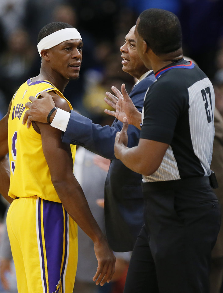 Photo - Los Angeles' Rajon Rondo (9) talks to official Mitchell Ervin (27) as Lakers assistant coach Lionel Hollins, middle, tries to get Rondo to leave the floor after being ejected for a Flagrant 2 foul in the fourth quarter during an NBA basketball game between the Oklahoma City Thunder and the Los Angeles Lakers at Chesapeake Energy Arena in Oklahoma City, Friday, Nov. 22, 2019. The Lakers won 130-127. [Nate Billings/The Oklahoman]