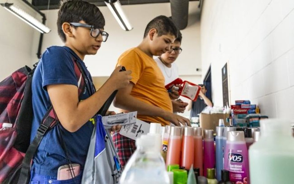 Photo -  Tornado victims, from left, Yahir Gallegos, 12, Michael Castanon, 12, and Daniel Castanon, 13, collect supplies at the Red Cross Shelter inside the Jenks Simmons Fieldhouse in El Reno, Okla. on Monday, May 27, 2019. The EF3 tornado hit the area on Saturday night killing two people and injuring many others. (Chris Landsberger/The Oklahoman,via AP)
