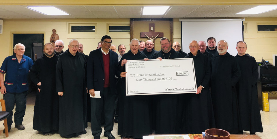 Photo -  Mohan Chandran, the Rev. Paul Zahler, O.S.B., and Abbot Lawrence Stasyszen, O.S.B., hold a check symbolizing a donation Benedictine monks at St. Gregory's Abbey made to Zahler's nonprofit organization. [Photo by Theresa Bragg]