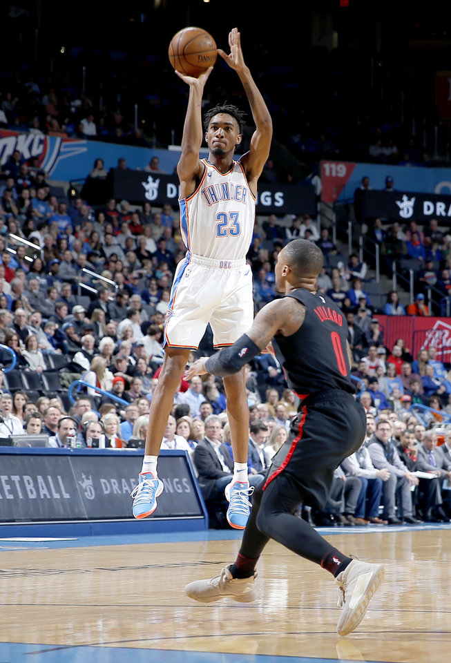Photo - Oklahoma City's Terrance Ferguson (23) shoots as Portland's Damian Lillard (0) defends during the NBA basketball game between the Oklahoma City Thunder and the Portland Trail Blazers at Chesapeake Energy Arena in Oklahoma City, Tuesday, Jan. 22, 2019. Photo by Sarah Phipps, The Oklahoman
