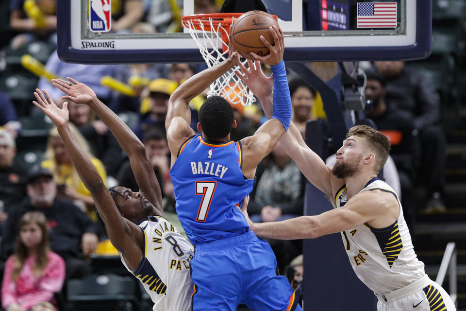 Photo - Oklahoma City Thunder forward Darius Bazley (7) shoots over Indiana Pacers guard Justin Holiday (8) and forward Domantas Sabonis (11) during the second half of an NBA basketball game in Indianapolis, Tuesday, Nov. 12, 2019. The Pacers won 111-85. (AP Photo/Michael Conroy)