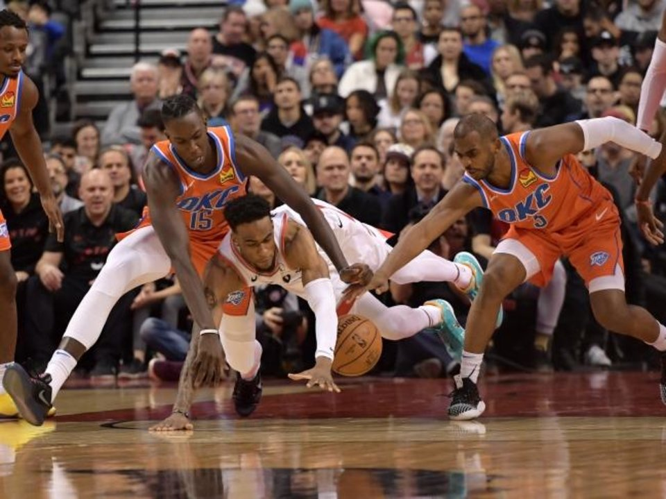 Photo -  Oklahoma City's Kevin Hervey, left, fights for a loose ball with Toronto's Oshae Brissett, center, during a recent game. Hervey is the first player in Texas-Arlington history to play in the NBA. [Dan Hamilton/USA TODAY Sports]