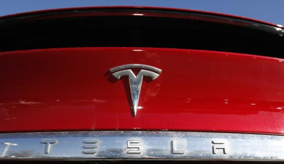 Photo -  The Tesla logo sits on a 2020 Model X at a Tesla dealership in Littleton, Colo. [AP PHOTO]