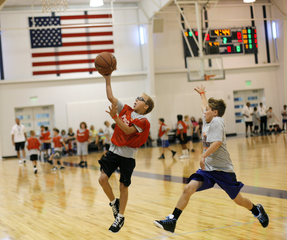 Photo - Tanner Holcomb, 11 of Oklahoma City, goes for a layup while Trey Buster, 11 of Springfield, Mo., tries to block during the second day of the Kevin Durant basketball camp at Heritage Hall in Oklahoma City, Thursday, June 30, 2011.  Photo by Garett Fisbeck, The Oklahoman