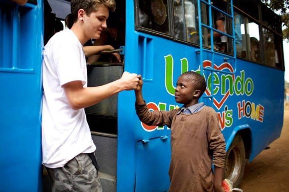 Photo -  A volunteer fist-bumps a child boarding an Upendo Children's Home bus in Juja, Kenya. Photo provided