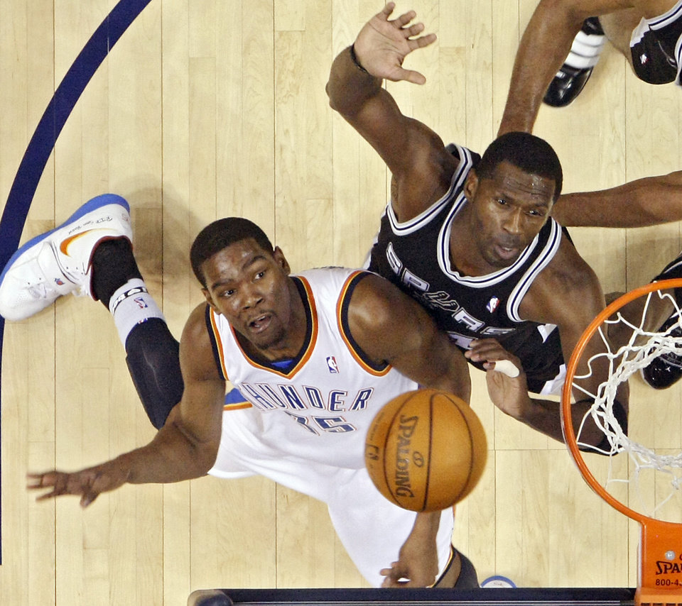 Photo - The Thunder's Kevin Durant puts up a shot past the Spurs' Antonio McDyess (34) during the NBA basketball game between the Oklahoma City Thunder and the San Antonio Spurs at the Ford Center on Monday, March 22, 2010, in Oklahoma City, Okla.  Photo by Chris Landsberger, The Oklahoman
