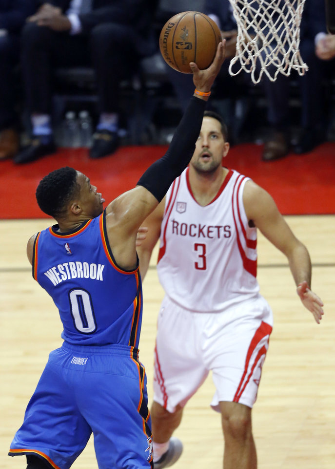 Photo - Oklahoma City's Russell Westbrook (0) goes to the basket as Houston's Ryan Anderson (3) watches during Game 2 in the first round of the NBA basketball playoffs between the Oklahoma City Thunder and the Houston Rockets at the Toyota Center in Houston, Texas,  Wednesday, April 19, 2017.  Photo by Sarah Phipps, The Oklahoman