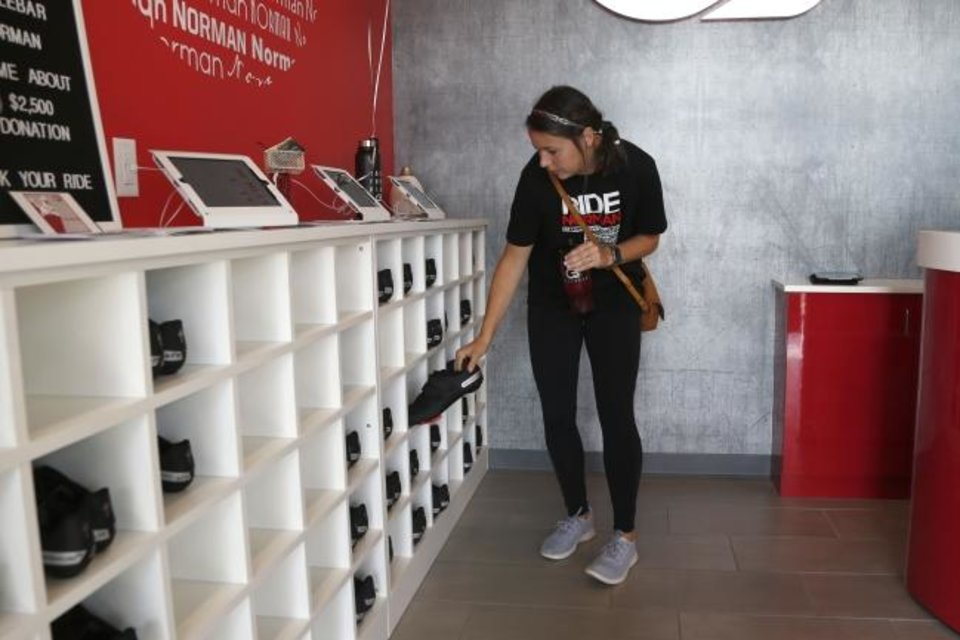 Photo -  A cyclist attending a class at the new CycleBar studio in Norman grabs a pair of shoes before getting on her reserved bike Thursday.[PAXSON HAWS/THE OKLAHOMAN]