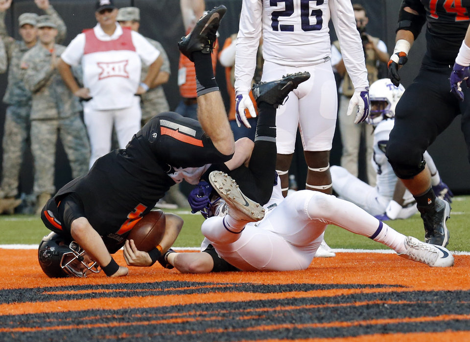 Photo - Oklahoma State's J.W. Walsh (4) scores a touchdown as TCU's Ty Summers (42) tackles him in the third quarter during the college football game between the Oklahoma State Cowboys (OSU) and TCU Horned Frogs at Boone Pickens Stadium in Stillwater, Okla., Saturday, Nov. 7, 2015. Photo by Sarah Phipps, The Oklahoman
