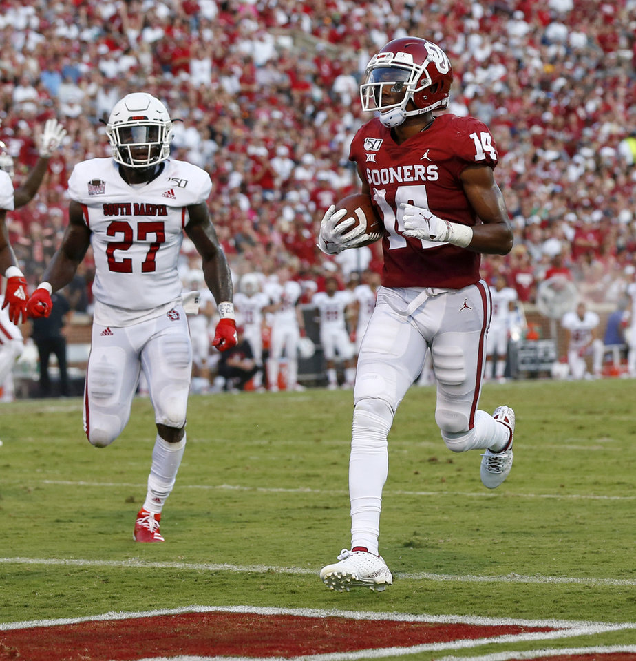 Photo - Oklahoma's Charleston Rambo (14) scores a touchdown in front of South Dakota's Jakari Starling (27) in the second quarter during a college football game between the Oklahoma Sooners (OU) and South Dakota Coyotes at Gaylord Family - Oklahoma Memorial Stadium in Norman, Okla., Saturday, Sept. 7, 2019. [Nate Billings/The Oklahoman]