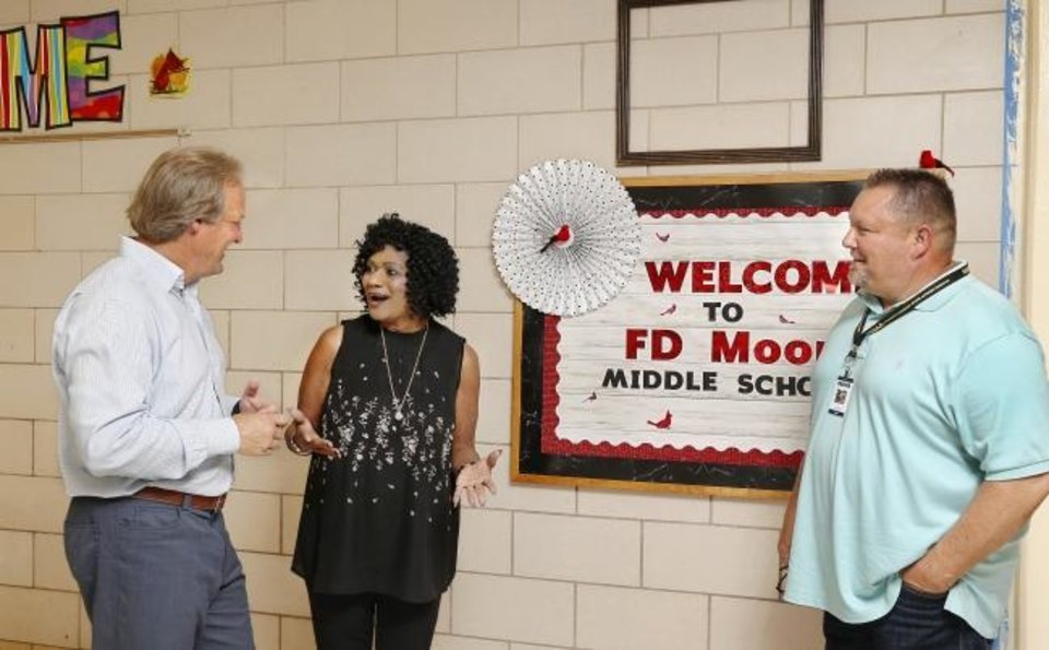 Photo -  Gloria Anderson, principal of F.D. Moon Middle School, talks to Tim McLaughlin, left, and Oklahoma City Public Schools Athletic Director Todd Dilbeck near the school's front office. McLaughlin and the local nonprofit Fields & Futures are overseeing work behind F. D. Moon to build athletic facilities. [Jim Beckel/The Oklahoman]